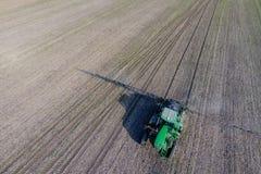 Tractor met scharnierend systeem om pesticiden te bespuiten Bevruchtend met een tractor, in de vorm van een aërosol, op het gebie royalty-vrije stock foto's
