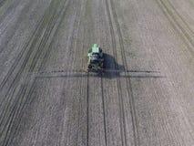 Tractor met scharnierend systeem om pesticiden te bespuiten Bevruchtend met een tractor, in de vorm van een aërosol, op het gebie stock afbeeldingen