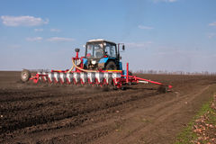 Tractor met sower op het gebied Stock Afbeelding
