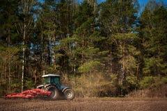 Tractor met wieden-machine op rand van geploegd gebied bij bos stock afbeelding