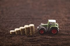 Tractor miniature with coins on fertile soil land. Green tractor miniature with golden coins on fertile soil land stock photography