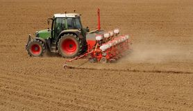 Tractor with a modern sowing seeds machine in a newly plowed field in springtime. Side back view, with only plowed land as a background Royalty Free Stock Image