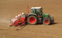 Tractor with a modern sowing seeds machine in a newly plowed field in springtime. Side view. Plowed land on background.  royalty free stock image