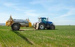 Tractor moderno azul que tira de un rociador de la cosecha Foto de archivo