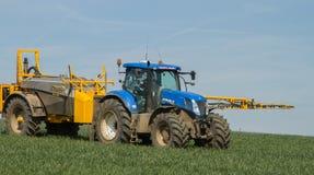 Tractor moderno azul que tira de un rociador de la cosecha Imagen de archivo