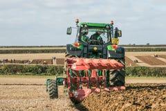 Tractor moderno de John Deere que tira de un arado Foto de archivo libre de regalías
