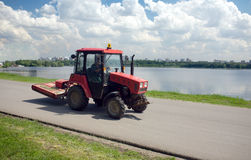 Tractor moves down on a road against city landscape Royalty Free Stock Images