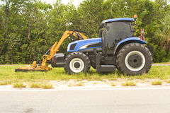 Tractor with mower arm attached. A small blue tractor with a mowing arm attached Royalty Free Stock Photography