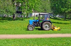 Tractor with mower cutting grass Royalty Free Stock Images
