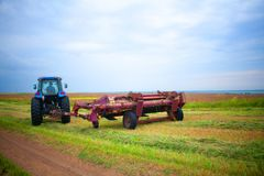 Tractor with mower in the field of sainfoin and alfalfa. A tractor with a mower in the field of sainfoin and alfalfa mowing grass harvesting the field in summer Royalty Free Stock Images