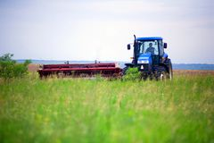 Tractor with mower in the field of sainfoin and alfalfa. A tractor with a mower in the field of sainfoin and alfalfa mowing grass harvesting the field in summer Royalty Free Stock Photography
