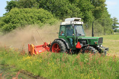 Tractor mowing grass. Mowing bank of a ditch Stock Image