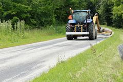 Tractor mowing the grass on the side of a country road royalty free stock image