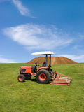 Tractor mowing green field Stock Images