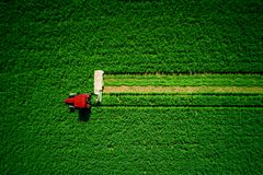 Tractor mowing green agriculture field, aerial drone view. Tractor mowing green field, aerial view stock photography