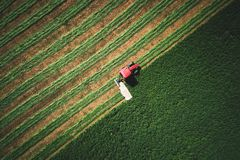 Tractor mowing green agriculture field, aerial drone view royalty free stock photo