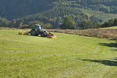 Tractor mowing mountain meadow Royalty Free Stock Photos