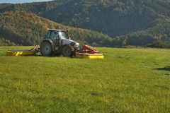 Tractor mowing mountain meadow Royalty Free Stock Photo