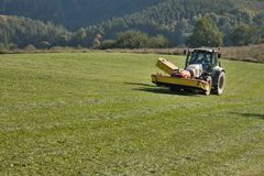 Tractor mowing mountain meadow. In Czech Republic Stock Photography