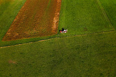 Tractor mowing pasture on big field of neatly cultivated land Stock Photos