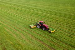 Tractor mows the grass on a green field aerial view stock photos