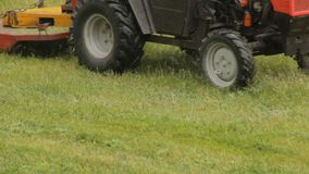 Tractor mows the grass in the rain, close-up. Lawn mower stock video