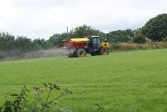 Tractor and Muck Spreader Fertiliser. Yellow Tractor and Muck Spreader Fertiliser Spraying Stock Images