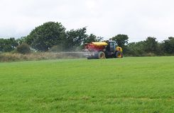 Tractor and Muck Spreader Fertiliser. Yellow Tractor and Muck Spreader Fertiliser Spraying Royalty Free Stock Images
