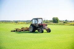 Tractor with a nozzle for care of a field lawn for a horse polo in work. The cut-off grass takes off from mechanical parts of a no. Zzle. Green flat field. Sky stock photo