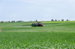 Tractor nozzles fertilizing crops field Royalty Free Stock Image