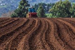 Tractor op aardappelgebied Stock Afbeelding