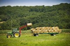 Tractor op de balen van de landbouwbedrijflading in hooi op aanhangwagen Stock Afbeeldingen