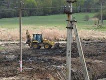 Tractor op de bouwwerf tegen de rivier, de bomen en de hemel stock fotografie