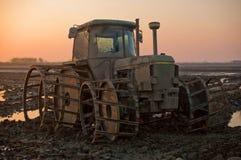 Tractor op de modder bij zonsondergang in padievelden stock fotografie