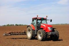 Tractor op een landbouwgrond stock afbeelding