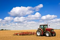 Tractor op geploegd gebied Stock Afbeeldingen
