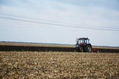 Tractor op het gebied in het midden van bebouwing stock fotografie