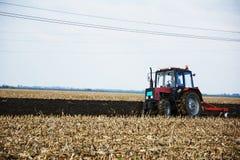 Tractor op het gebied in het midden van bebouwing stock foto
