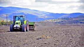 Tractor op het werk aangaande landbouwgrond stock footage