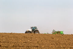 Tractor operates on horizon line ploughed field on foreground Stock Image