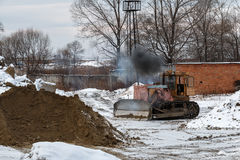 The tractor operator starts the bulldozer. The bulldozer driver in a warehouse of inert materials Royalty Free Stock Image