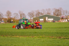 Tractor operator on the tractor carries out field work Stock Photos