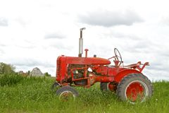 Tractor Parked in Grassy Field Royalty Free Stock Photo