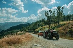Tractor passing through roadway on hilly landscape. Serra da Estrela, Portugal - July 14, 2018. Tractor passing through road on hilly landscape at the Serra da stock photo