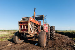 Tractor in a peat bog field Royalty Free Stock Image