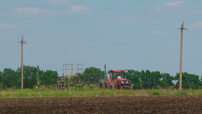 Tractor Planting Crops In The Field. One red tractor with seeder moving backwards while planting the seeds on the field between two electric poles. Plowed soil stock footage