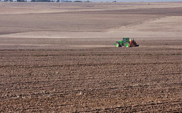Tractor planting wheat. Tractor and planter planting wheat on winter farm field Stock Images