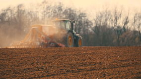 Tractor ploegend gebied bij zonsondergang stock footage