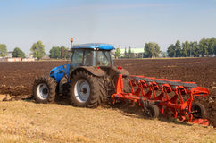 Tractor with plough. Agriculture tractor with plough in field Stock Image