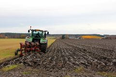 Tractor and plough on a Field in Autumn Stock Photo